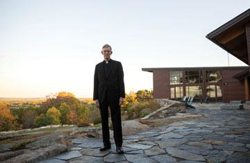 : Fr. Boroughs posing for photo in front of the Joyce Contemplative Center