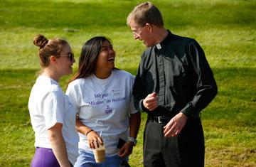 Fr. Boroughs conversing with two students