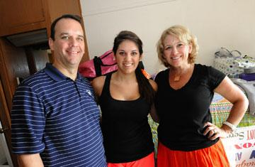 First-year student posing with parents in dorm room during move-in day