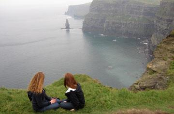 two students sitting on the grass on a cliff overlooking water