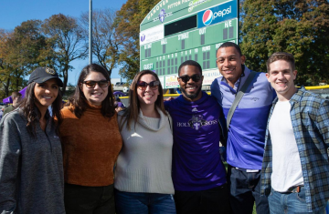 photo of a group of alumni in front of a scoreboard
