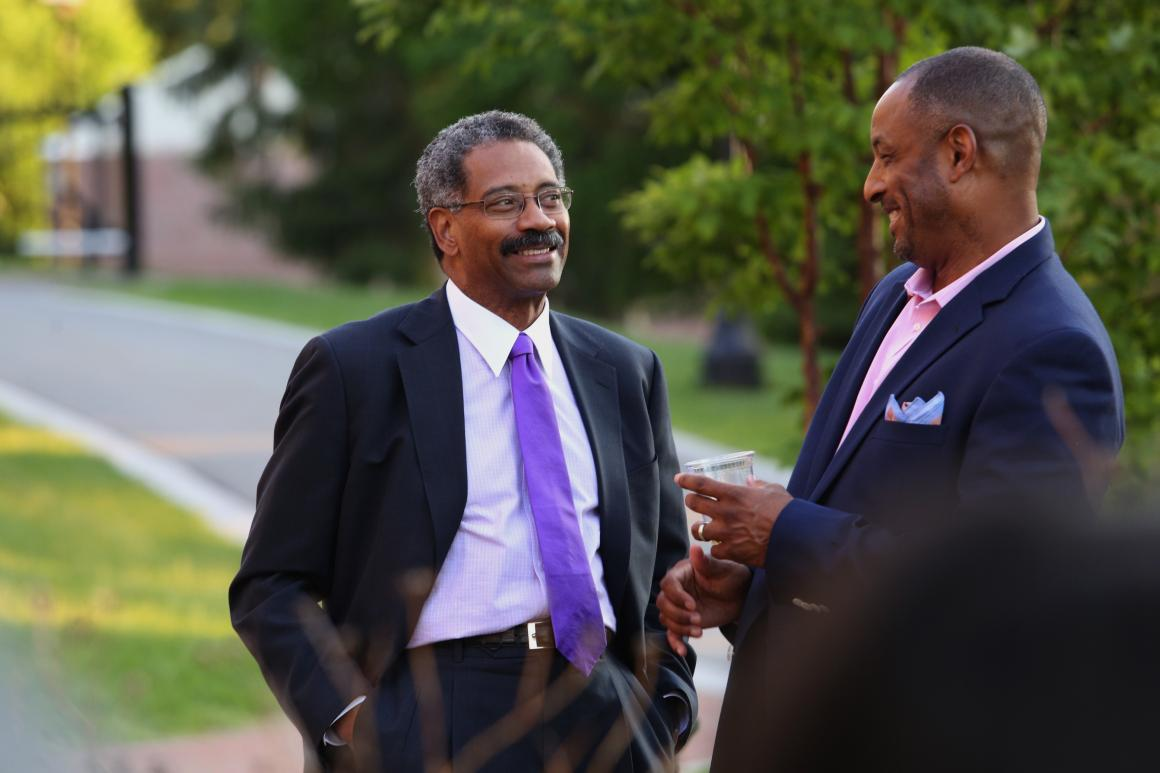Two men in business suits engaged in conversation