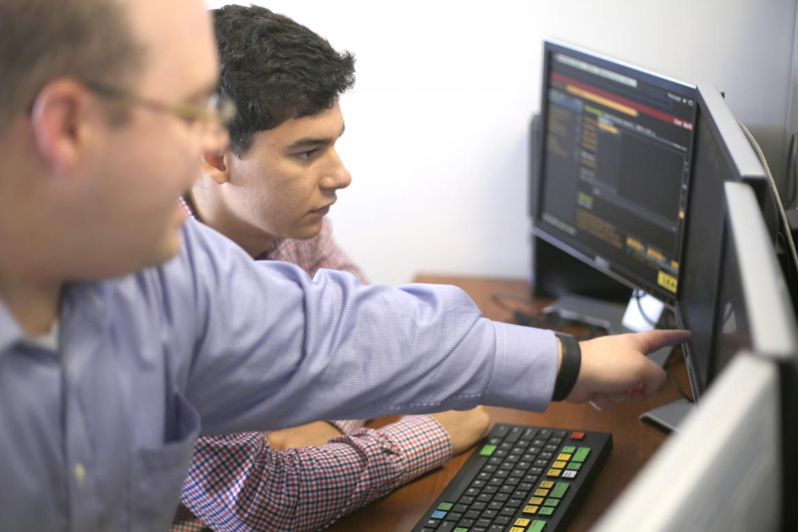 Two men looking at a computer screen on a desk