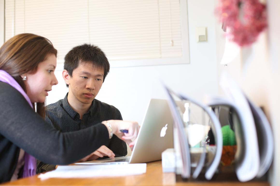 A teacher and student looking at a computer