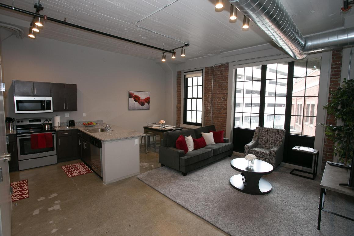 View of open concept apartment layout. From left to right, kitchen, dining area, living room.