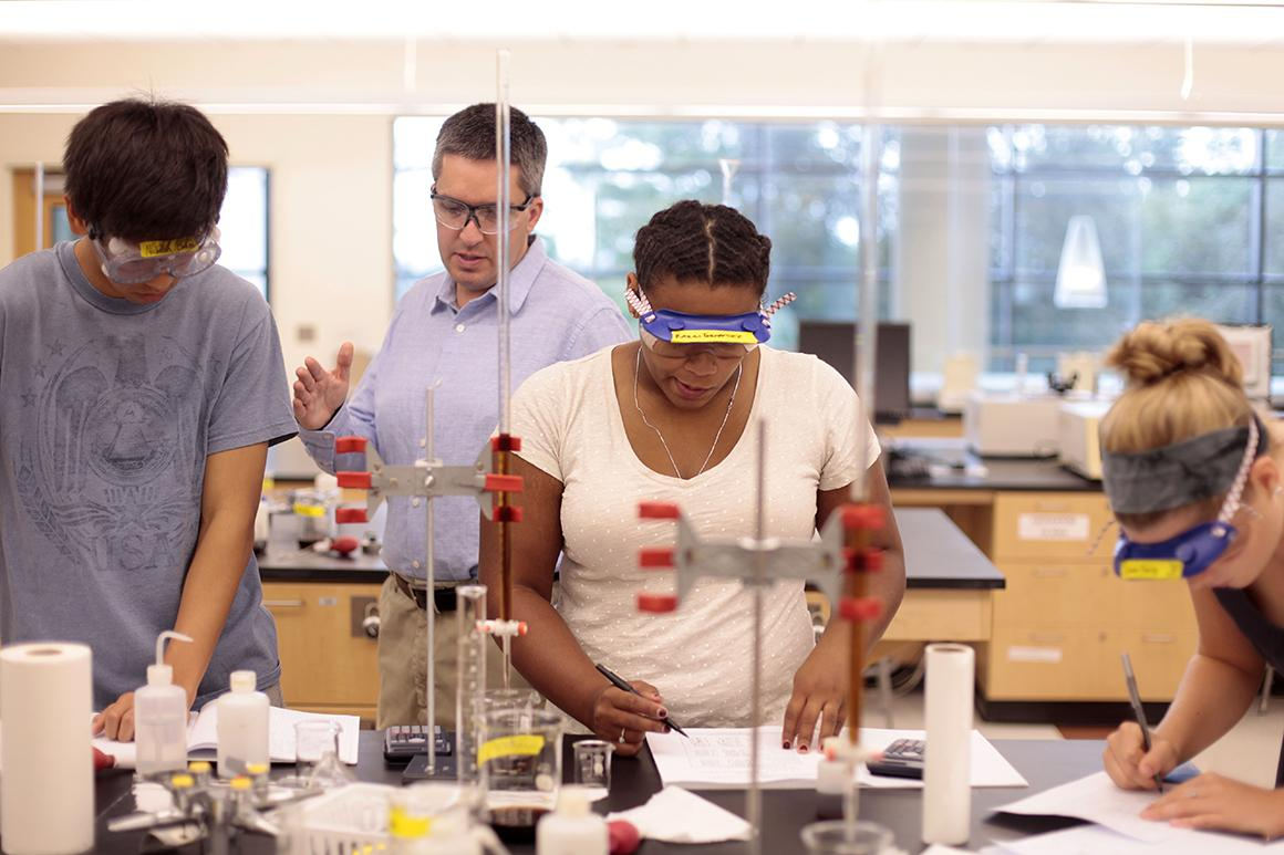 Ken Mills, professor of chemistry, works with students in his lab.