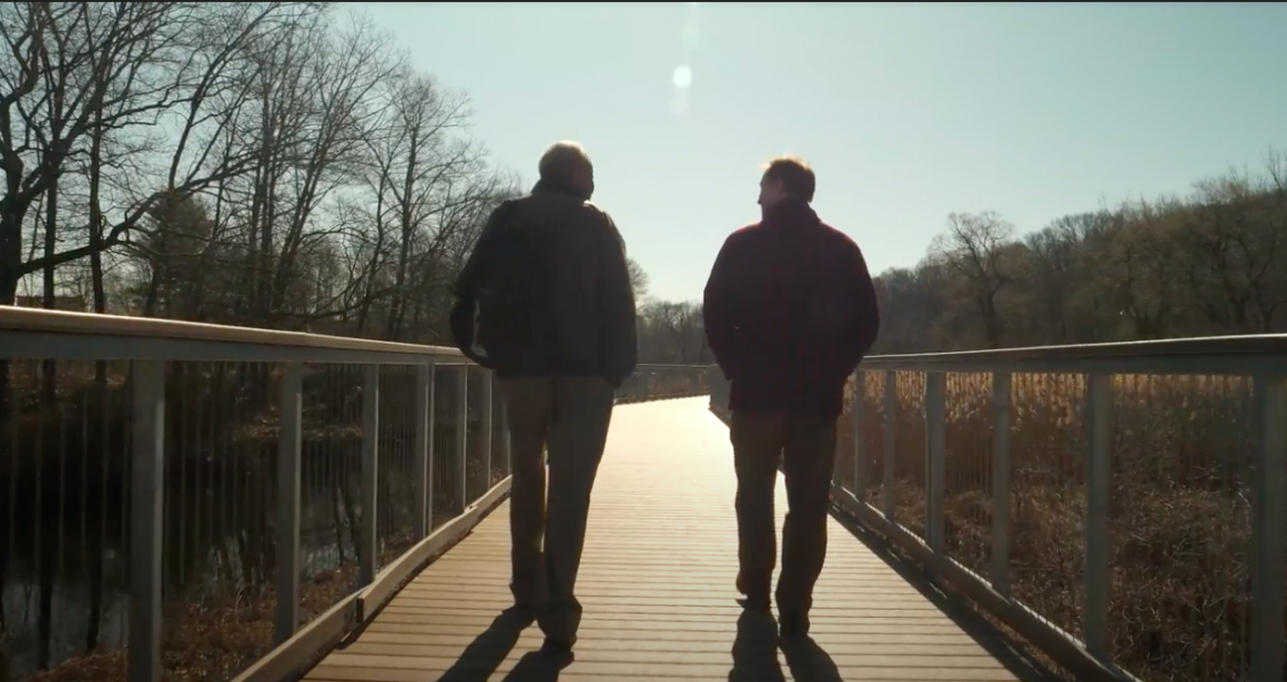 Thomas Doughton and Colin Novick walk away from the camera, silhouetted by the sun, on the boardwalk along the Blackstone Heritage Corridor.
