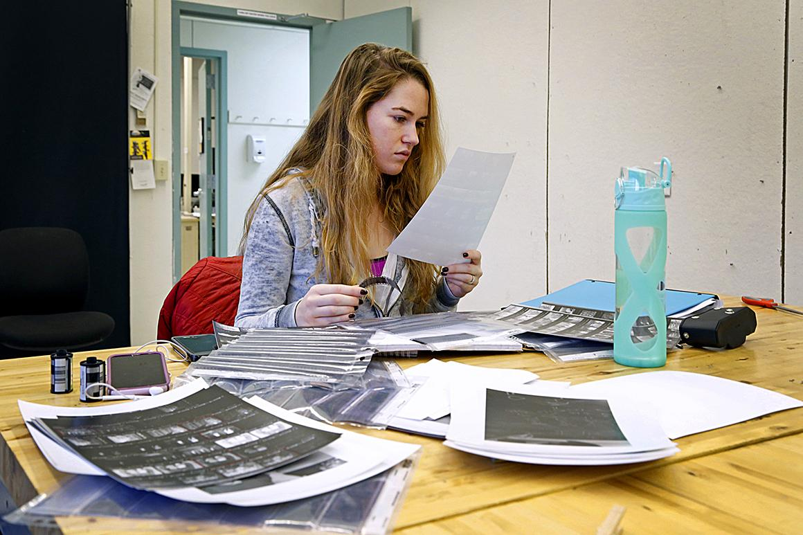 student at a desk looking at a photo