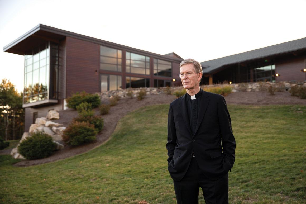 Alt text: Looking away from the camera, Fr. Boroughs, president of Holy Cross, stands in front of the Joyce Contemplative Center in West Boylston, Massachusetts.