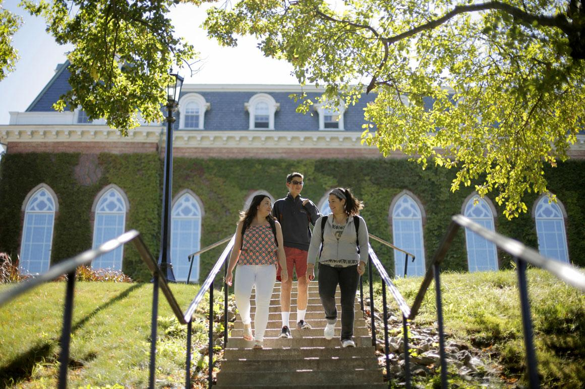 three students walking down flight of stairs to Kimball quad