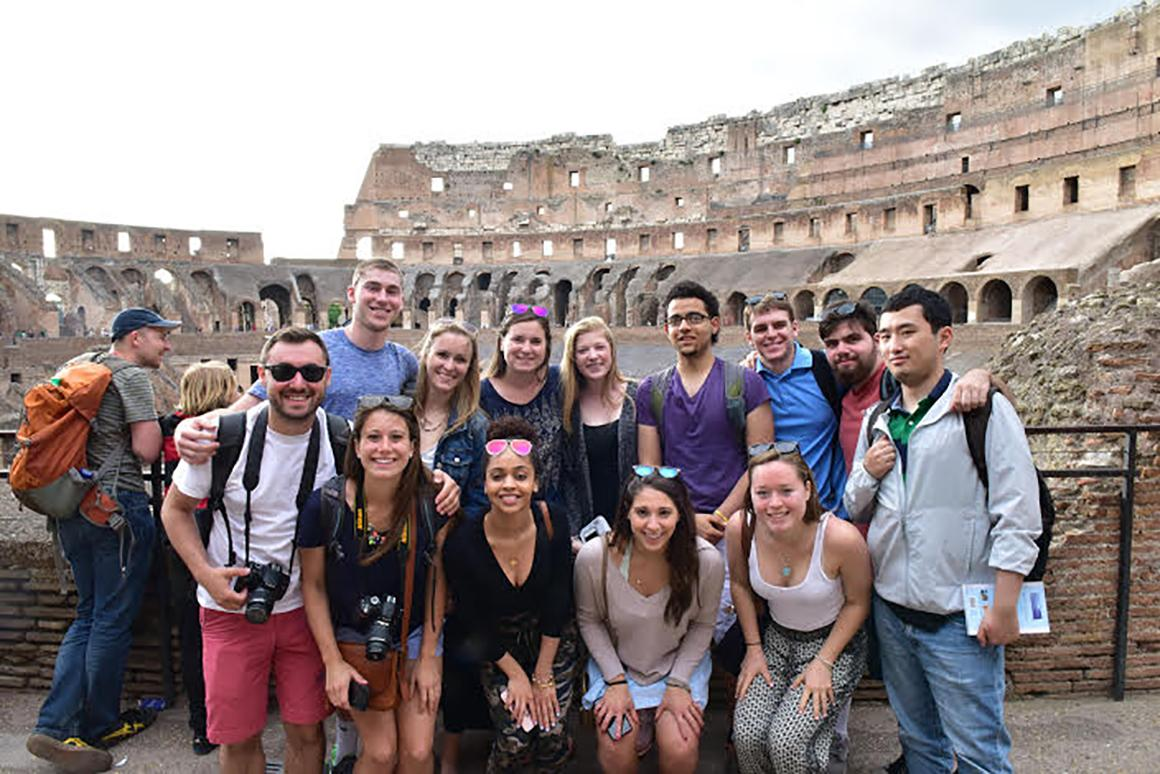a very large group of students posed in a roman amphitheater