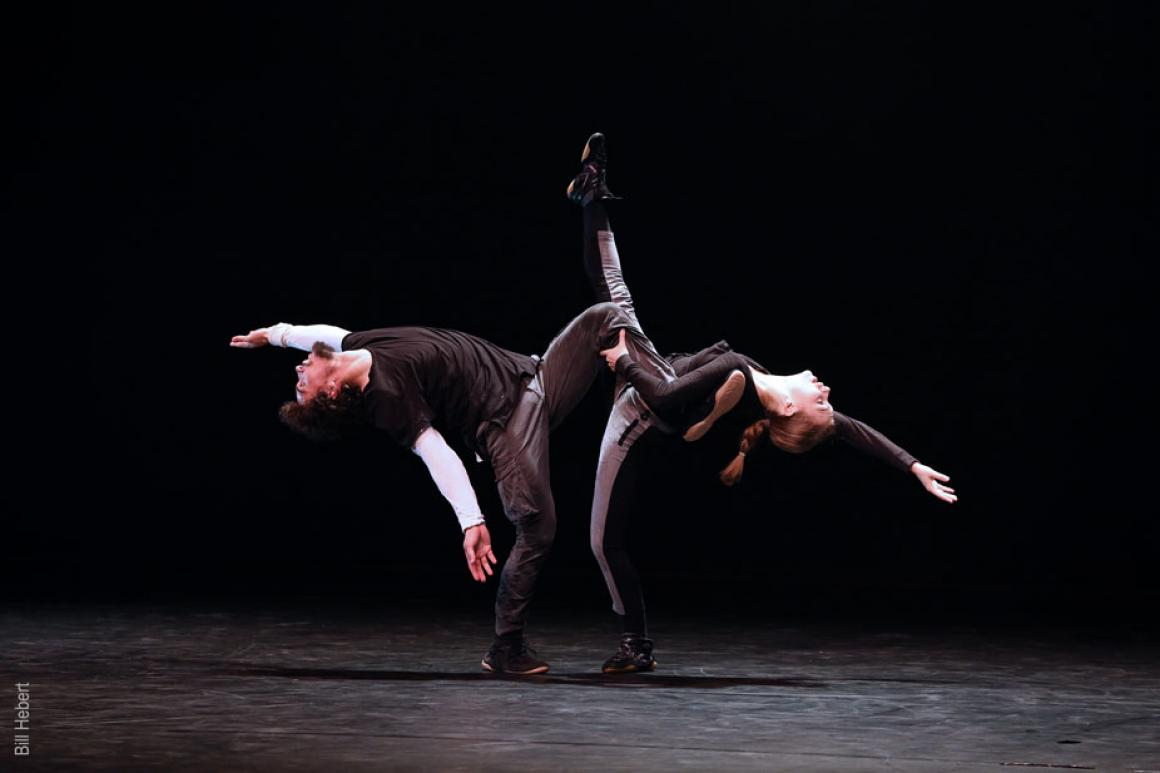 A male and female dancer facing each other both lean back balancing on one leg.