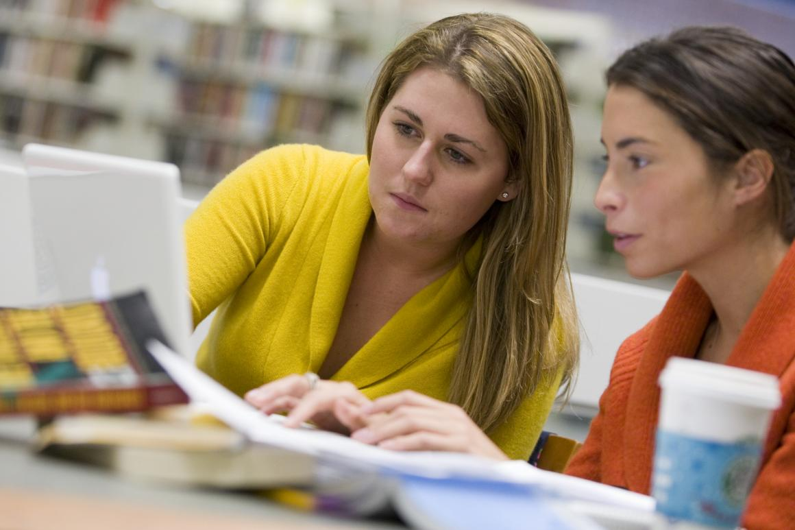 Two women looking at a laptop in a library