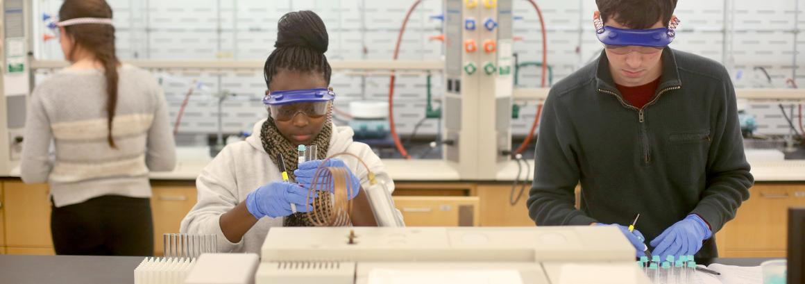 two students working in a lab wearing goggles