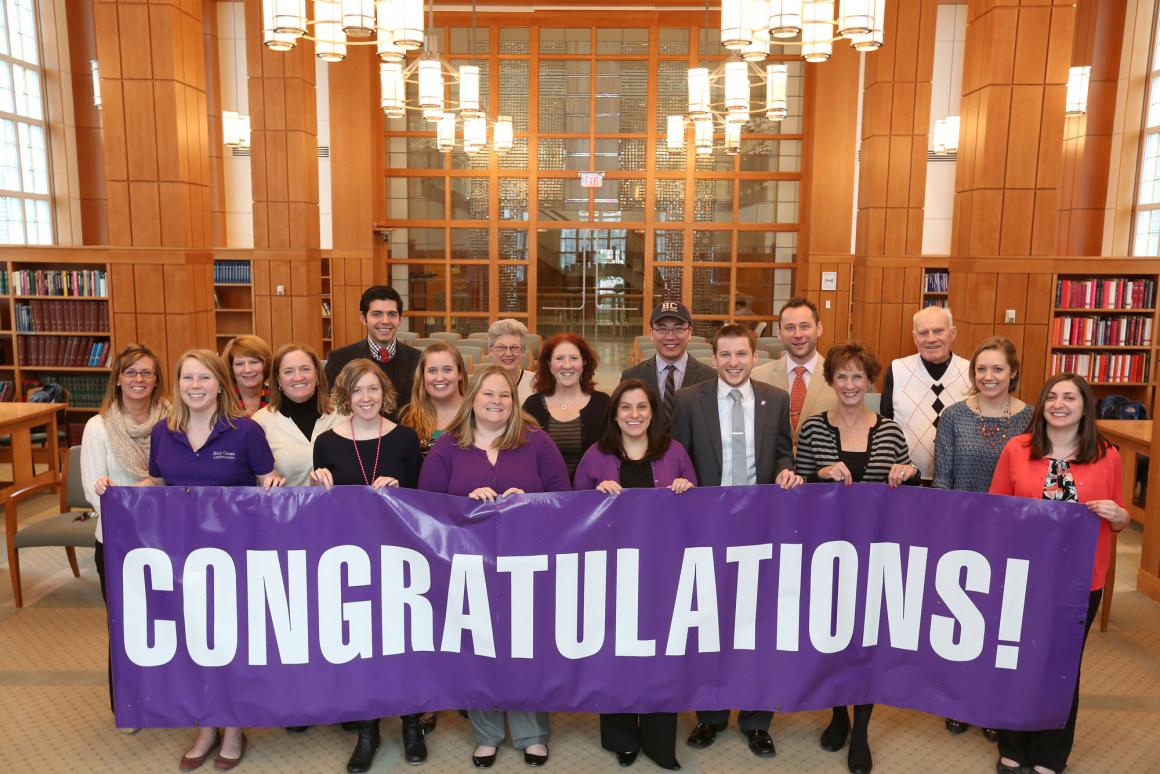"""Group of Admissions staff people holding up purple sign that reads, """"Congratulations"""""""