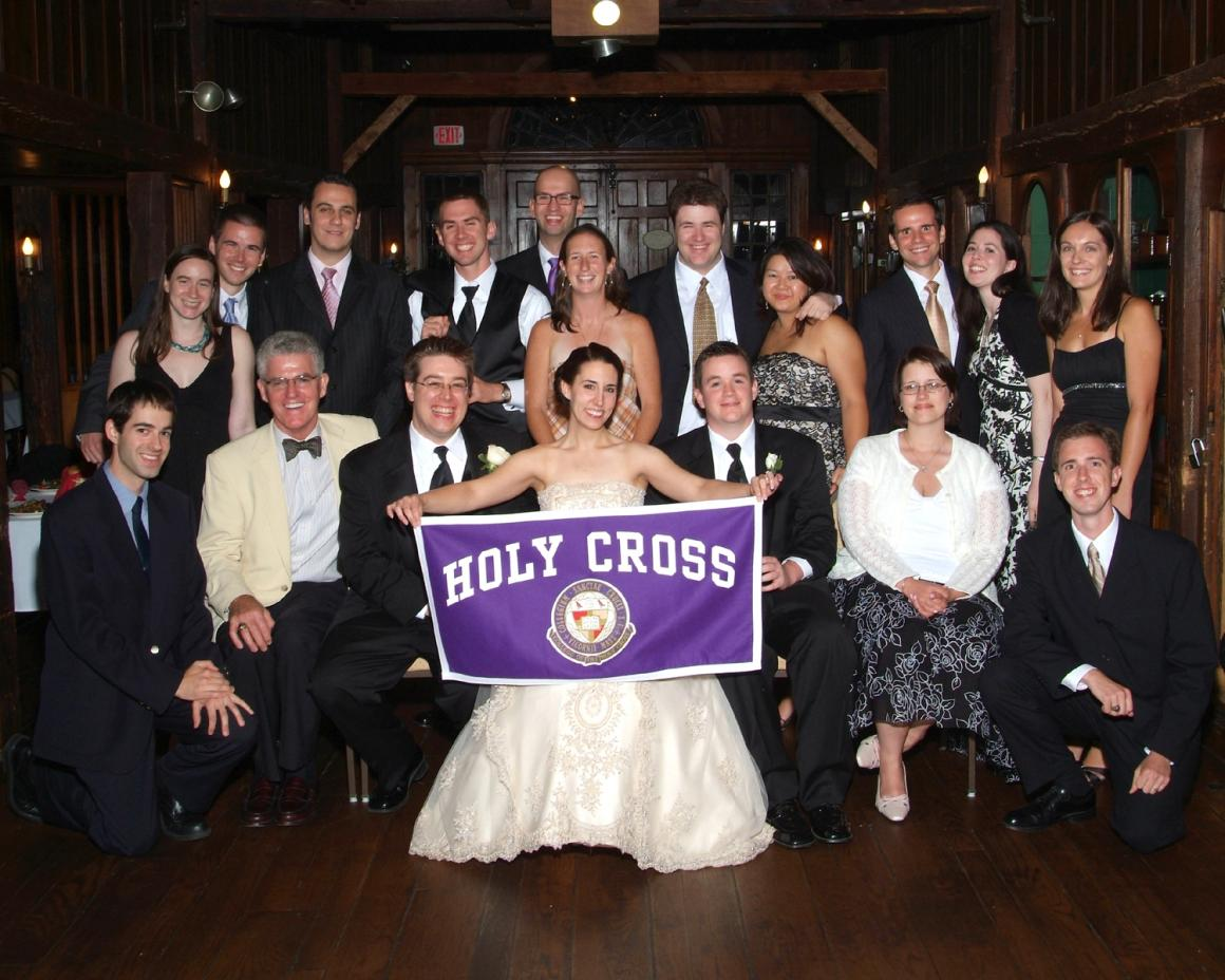 Bride and groom holding up Holy Cross banner and surrounded by wedding guests