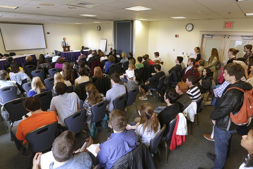 """Ryan Kingsley '17, in the English honors program, presents his senior thesis """"Bird on the Horizon"""" to a packed room in the Hogan Campus Center."""