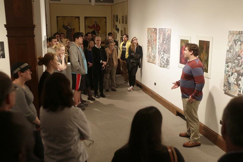 """Visual arts studio major John Silveira '17 with his """"Ghosts of the Deep"""" in the Cantor Art Gallery."""