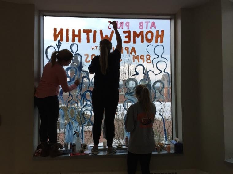 """Maria Claudia, Mickenzie, and Margaret work on a window display to promote """"Home Within"""""""