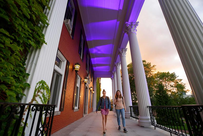 Students walk on the Fenwick porch, which is lit purple for the occasion. Photo by Tom Rettig