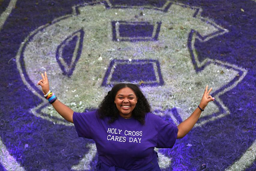 A student stands in front of the Holy Cross 175th logo painted on the grass. Photo by Tom Rettig