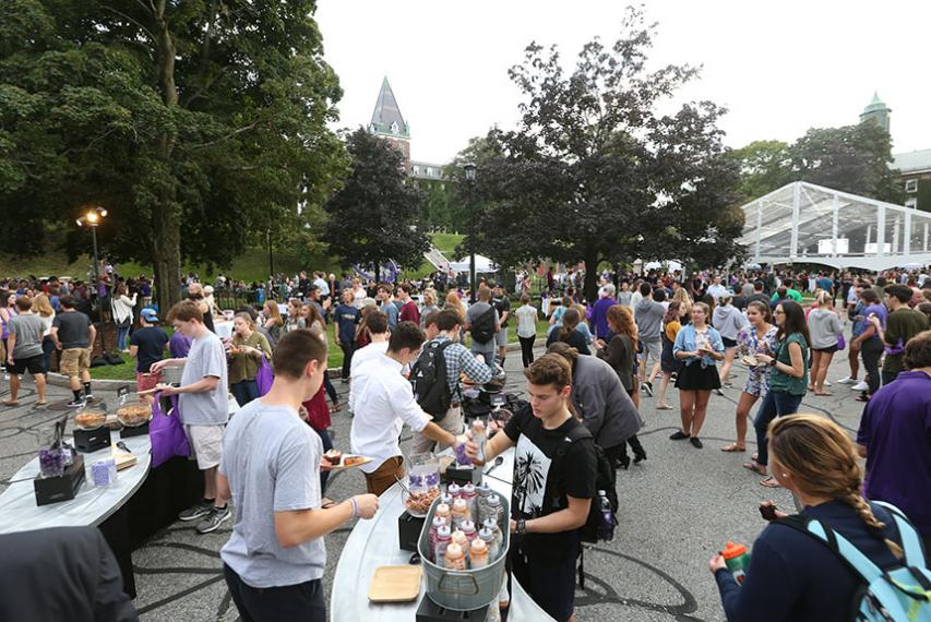 A crowd of people decorate donuts at one of the many food stations. Photo by Tom Rettig