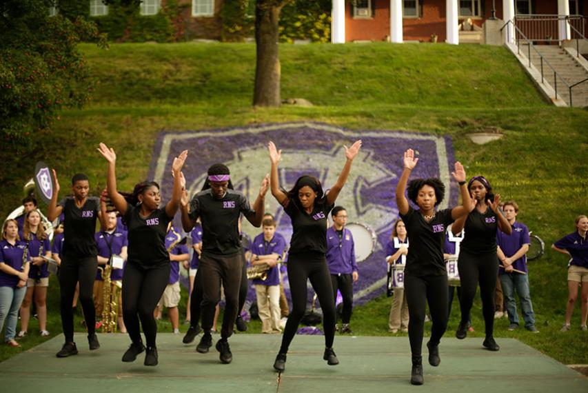 The Rhythm Nation Steppaz perform in front of a large Holy Cross 175th logo. Photo by Tom Rettig