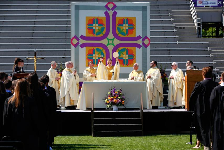 Fr. Boroughs presiding at Baccalaureate Mass on a dais on Fitton Field along with other Jesuits.