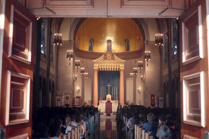 View of interior of St. Joseph Chapel from its entrance as Fr. Boroughs, president of Holy Cross, speaks at a podium before first-year students.