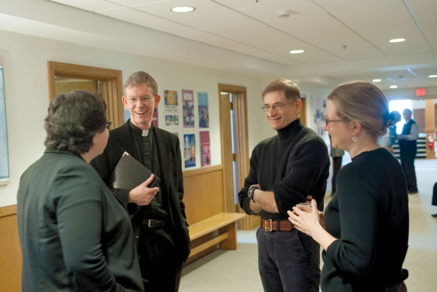 Fr. Boroughs, president of Holy Cross, talking with three members of the history department.