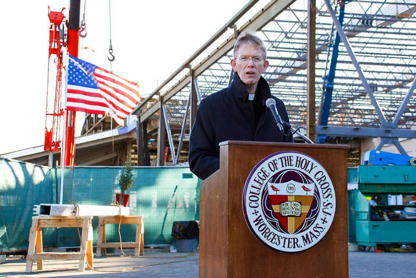 Fr. Borough, president of Holy Cross, speaking at a podium with construction of the Hart Center at the Luth Athletic Complex in the background.