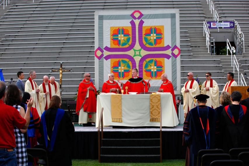 Fr. Boroughs presiding at Mass of the Holy Spirit surrounded by other Jesuits on a dais on Fitton Field.