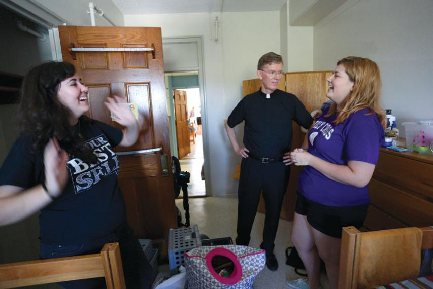 Fr. Boroughs, president of Holy Cross, talks with two students in a residence hall room on move-in day.