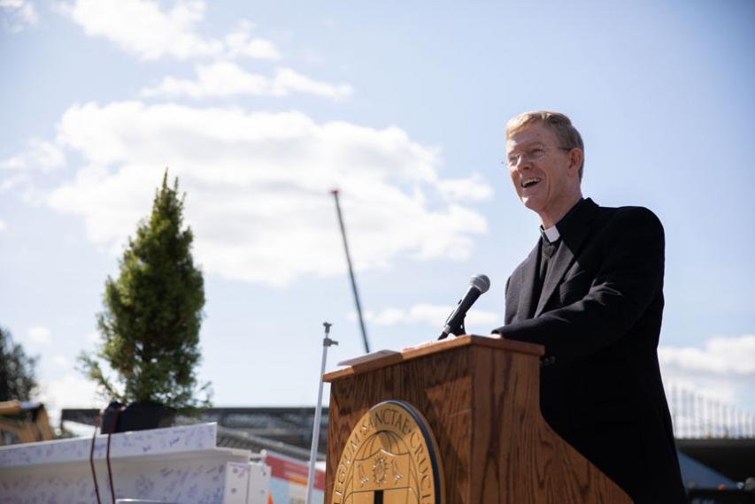 Fr. Boroughs, president of Holy Cross, at a podium in front of construction of the Joanne Chouinard-Luth Recreation and Wellness Center.